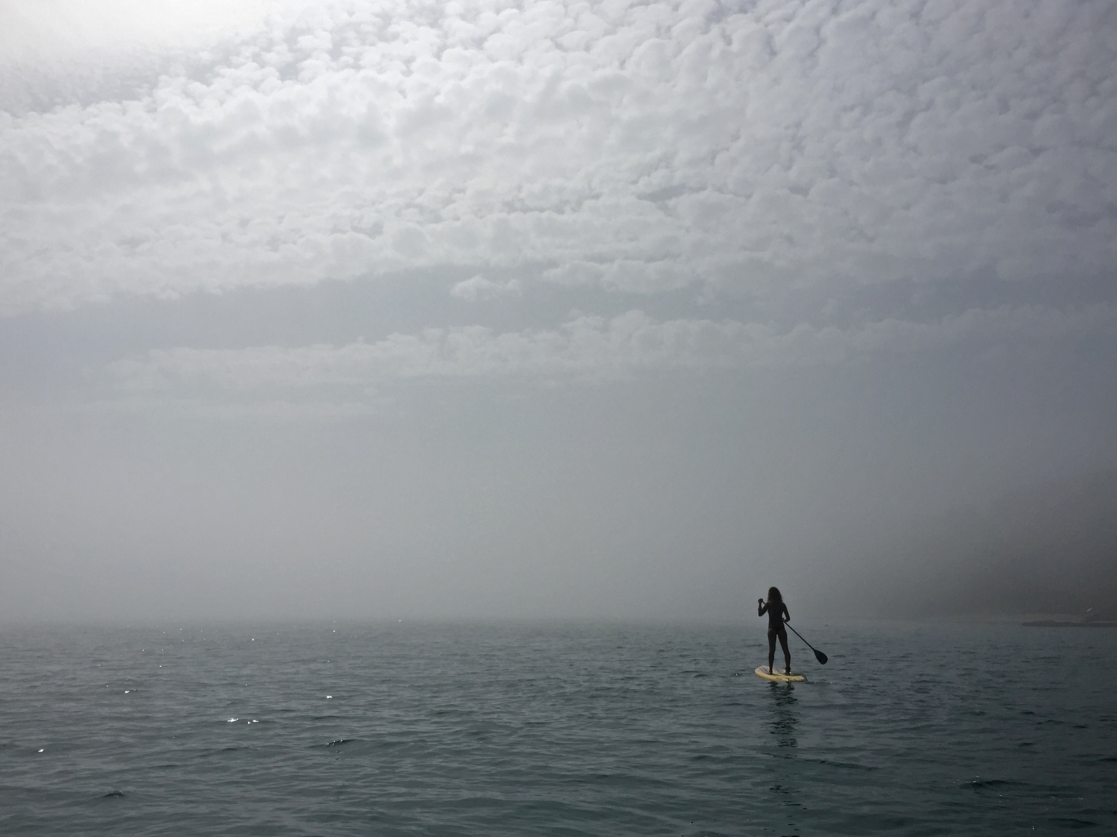 Paddleboarding in dense fog
